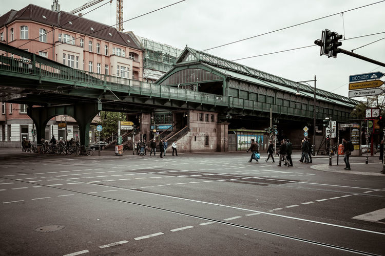 People on bridge in city against sky