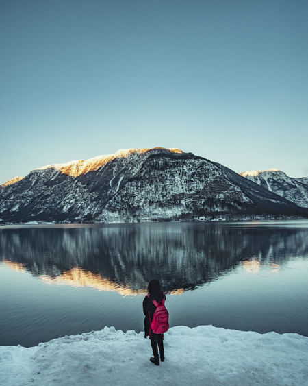 Rear view of woman standing by lake with snowcapped mountain reflection against sky
