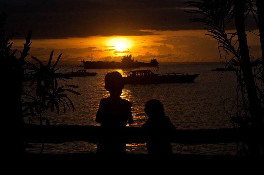 Beach Beauty In Nature Boys Childhood Horizon Over Water Lifestyles Nature Orange Color Outdoors Palm Tree People Real People Scenics Sea Silhouette Sky Sun Sunset Togetherness Tranquil Scene Tranquility Tree Water