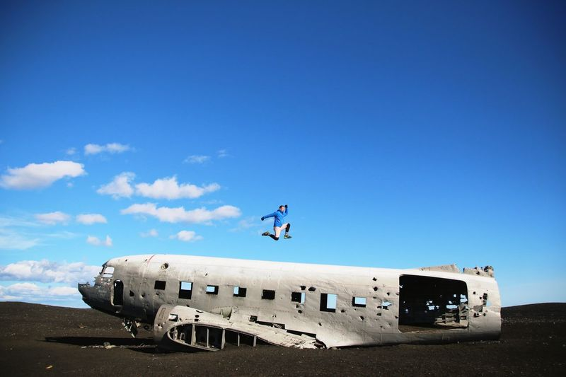 Full length of man jumping over airplane wreck against clear sky