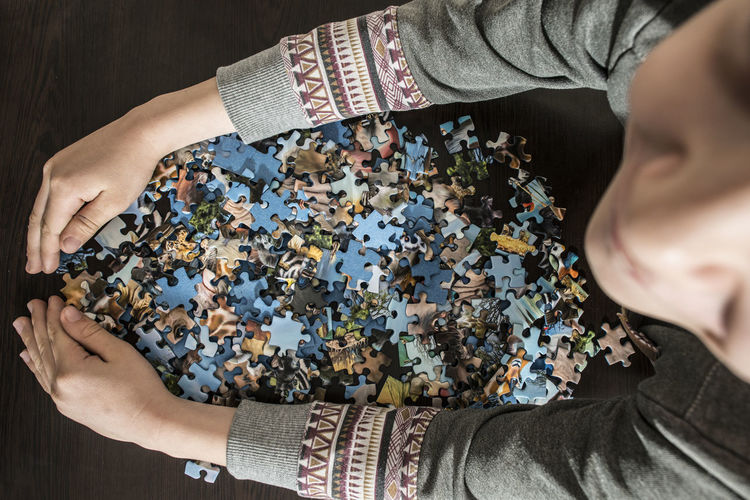 High angle view of child with jigsaw pieces