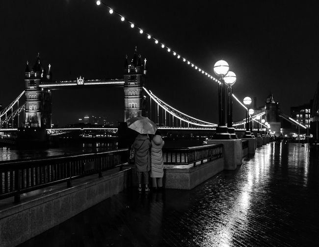 Rear view of people on suspension bridge at night
