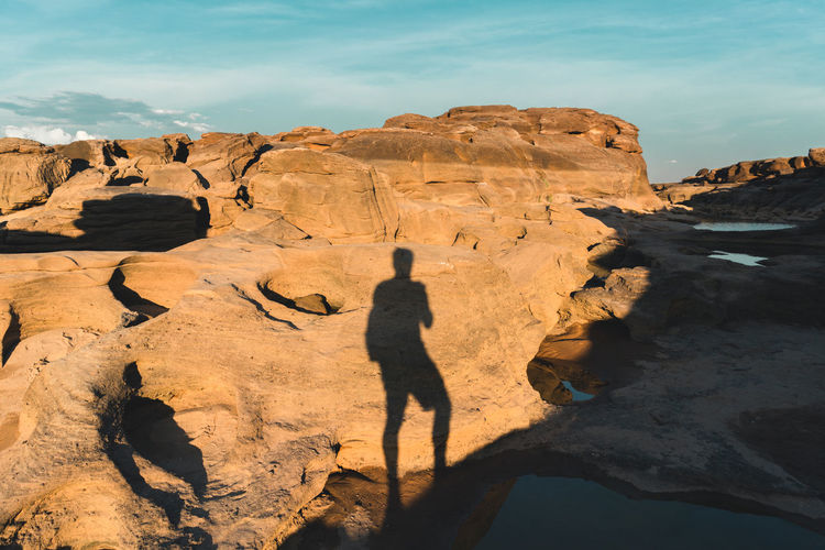 Rear view of man on rock formations against sky