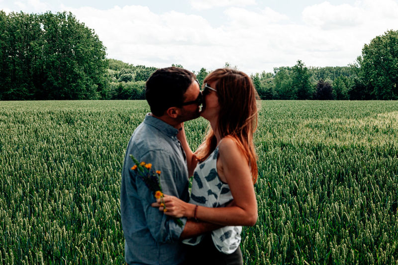 Naturally defocused caucasian couple in casual clothes kissing in a greenfield - focus on the field