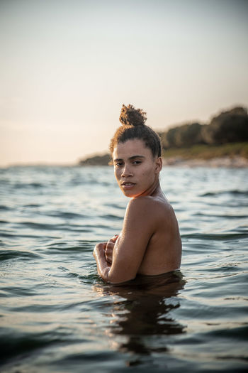 Portrait Of Woman In Sea Against Sky During Sunset
