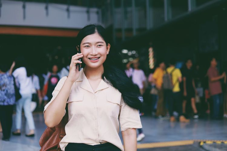 Smiling Front View Happiness Standing Focus On Foreground Young Adult One Person Mobile Phone Real People Using Phone Looking At Camera Three Quarter Length Women Wireless Technology Clothing Telephone Technology Holding Young Women Leisure Activity Beautiful Woman Hairstyle Outdoors