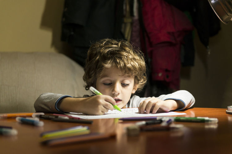 Boy drawing on paper at home