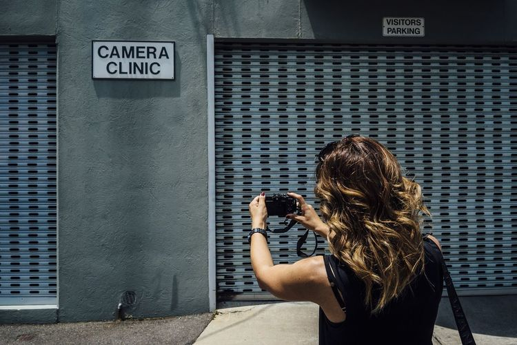 Rear view of woman photographing shutters