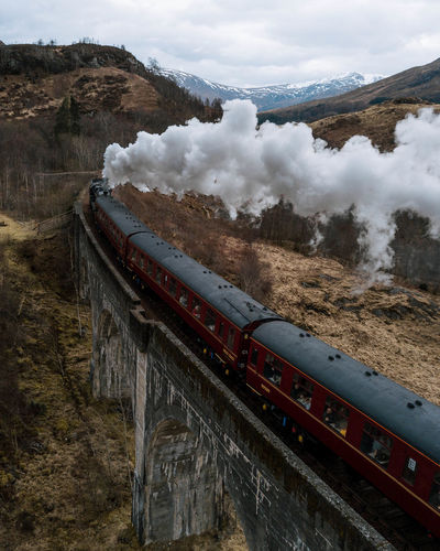 The Great Outdoors - 2018 EyeEm Awards Cloud - Sky Day Environment Locomotive Mode Of Transportation Mountain Nature No People Passenger Train Pollution Public Transportation Rail Transportation Railroad Track Sky Smoke - Physical Structure Steam Train Track Train Train - Vehicle Transportation Travel