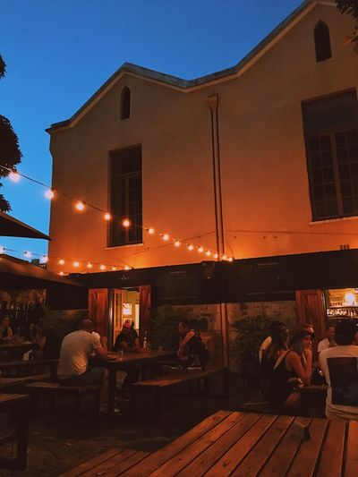 People enjoying an outdoor bar, Cape Town. Adult Architecture Building Exterior Built Structure Cafe City Evening Sky Friendship Group Of People Large Group Of People Lifestyles Men Night Outdoors People Real People Restaurant Sitting Sky Table Women