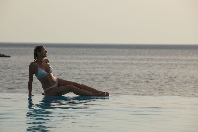 Full length of woman sitting by infinity pool against sea