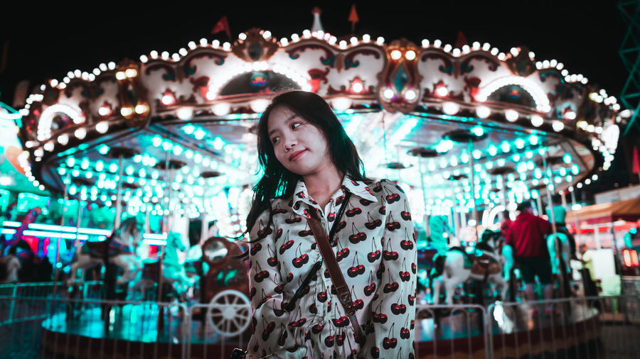 Portrait of young woman standing in illuminated carousel at amusement park