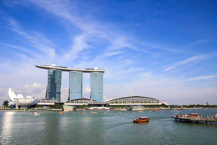 Low angle view of marina bay sands and boats moving on river