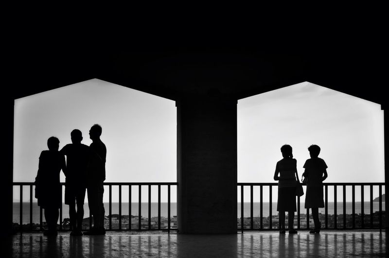 Silhouette of people standing on balcony