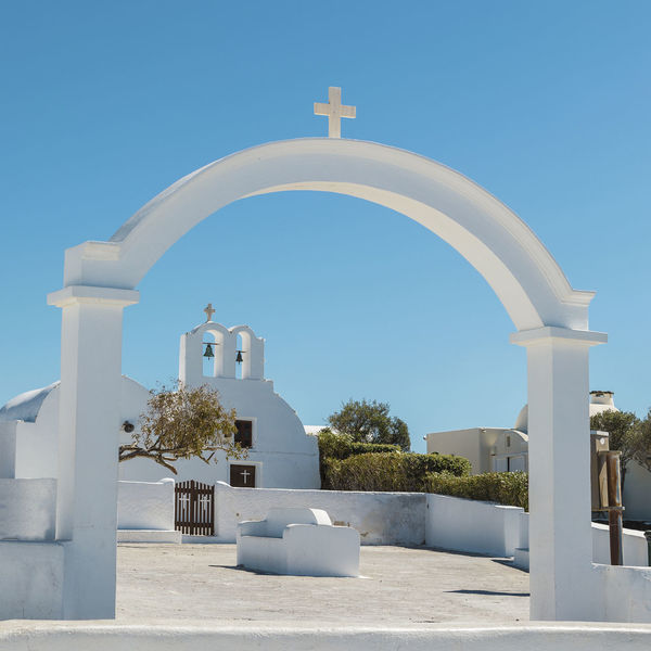 Gateway To Greek Church Arch Architecture Belief Building Building Exterior Built Structure Clear Sky Cross Day Greece Nature No People Orthodox Outdoors Place Of Worship Religion Santorini Sky Spirituality Sunlight White Color Whitewashed