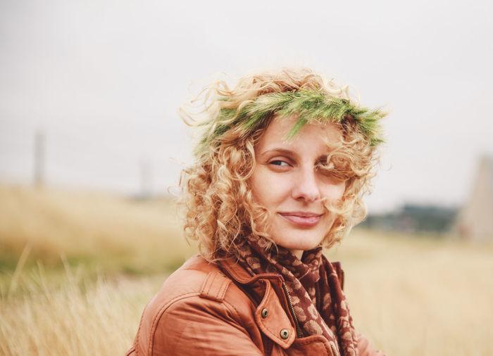 Portrait of woman wearing plant on field against sky