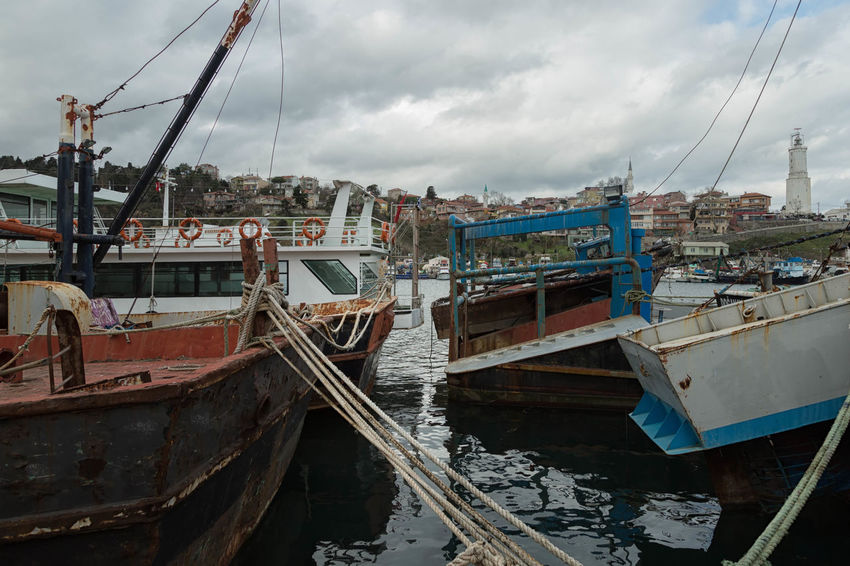 Rumeli Feneri is a small fishing village on the tip of the black sea in Turkey. A Wooden Boat: Vessel, Craft, Watercraft, Ship; Boat, Fishing Boat, Sail, Angler, Fisher, Fisheries Worker, Fishermen, Job, Work, Fishing Net, Dragnet, Drift Net, Trawl, Meshwork, Webbing, Tulle, Fishnet, Openwork, Lace, Latticework. Snare, Catch Cove, Inland, Inlet, Dock, Docks, Blue, Floater, Floaters, Float, Buoy Occupation, Profession, Trade, Position, Career, Work, Line Of Work, Livelihood, Sea, Ocean; Lake, River; Water, Sprinkle, Moisten, Dampen, Wet, Spray, Splash; Soak, Douse, Souse, Drench, Sky, Cloud, Cloudy, Day, Storm, Weather, Season, Cold, Turkey, Rumeli Feneri, Istanbul, Village, Harbor, Town, Small, Black Sea, Water, Sea,