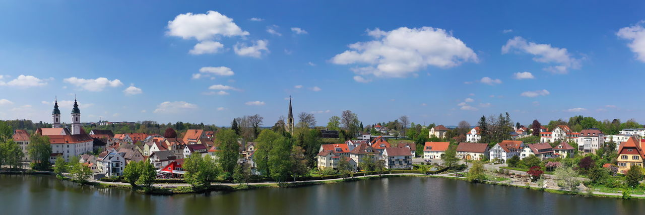 Panoramic view of river amidst buildings in town against sky