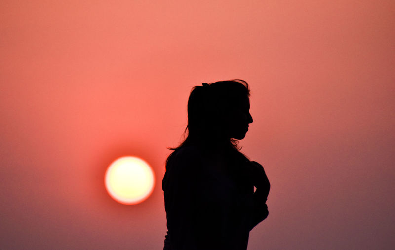 Silhouette woman standing against orange sun