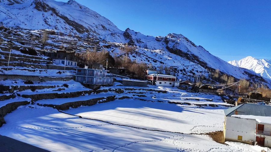 Snow covered buildings by mountain against sky