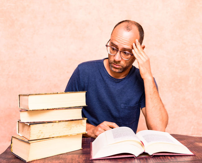 Portrait of man reading book on table