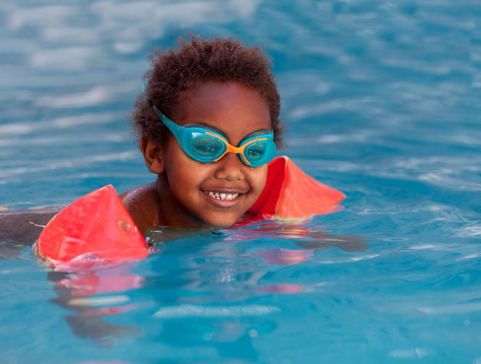 Portrait of smiling boy swimming in pool