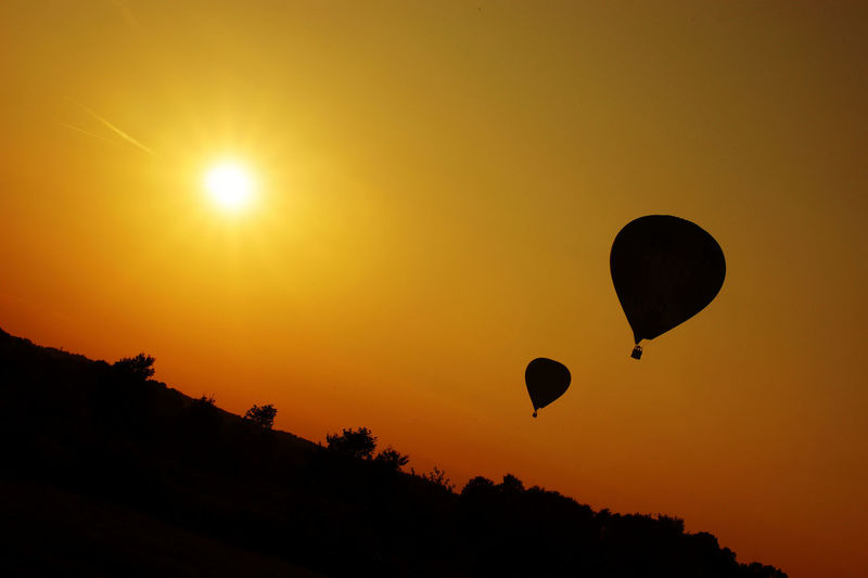 Adventure Astronomy Balloons Beauty In Nature Bright Lights Copy Space Day Flight Flying Hot Air Balloon Nature No People Outdoors Parachute Paragliding Silhouette Sky Sun Sunbeams Sunrise Sunset Sunset Silhouettes Symbolic  Warm Colors Warm Light
