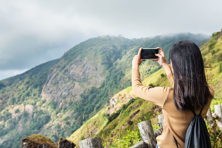Good phone signal ,rear view of man photographing on mountain