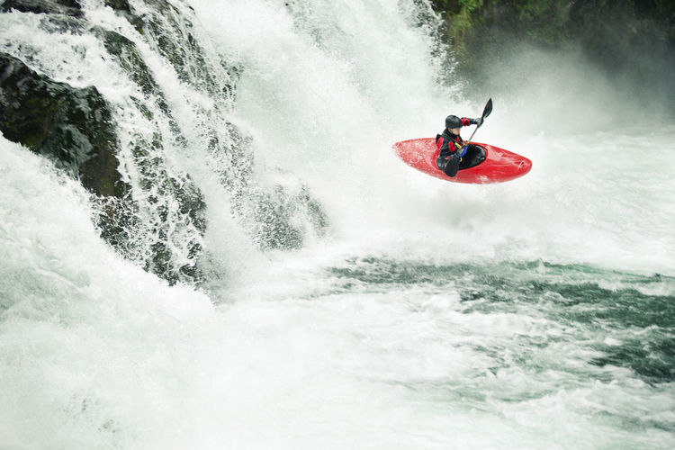 Man surfing on boat in river