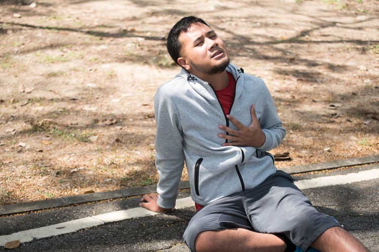 Man with chest pain sitting on road