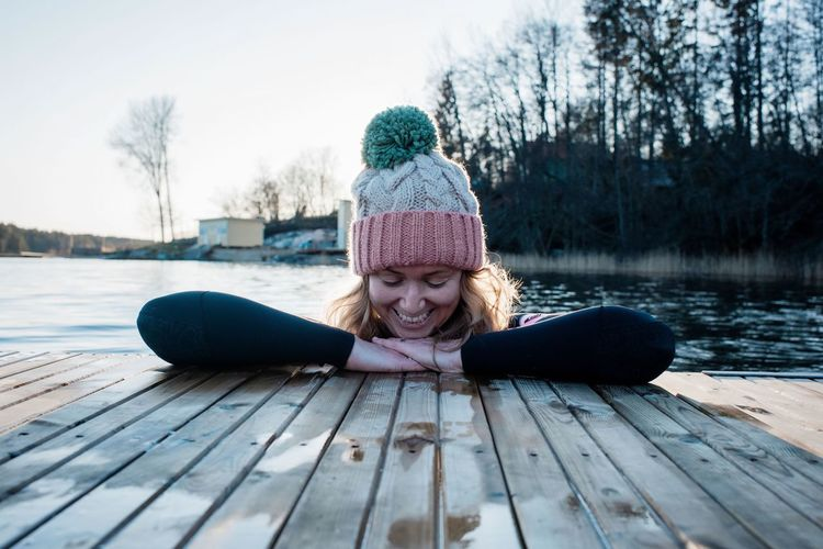 Woman sitting on wood by lake during winter