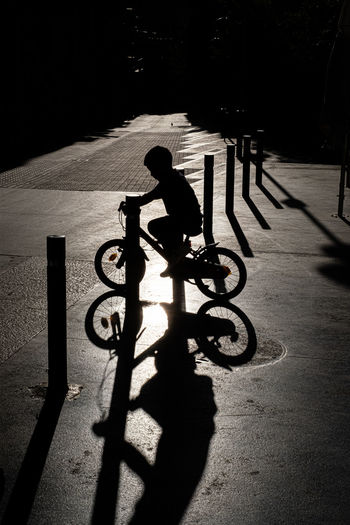 Silhouette man riding bicycle on city street