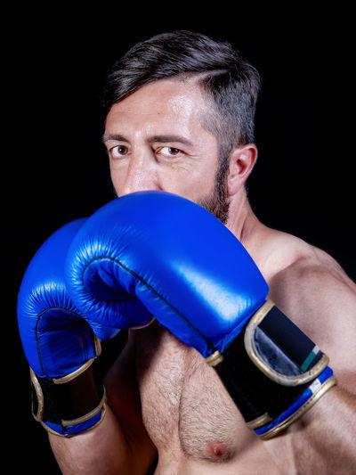 Portrait of boxer wearing blue gloves against black background