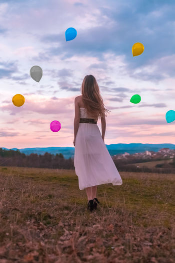 Rear view of woman with balloons moving up against sky