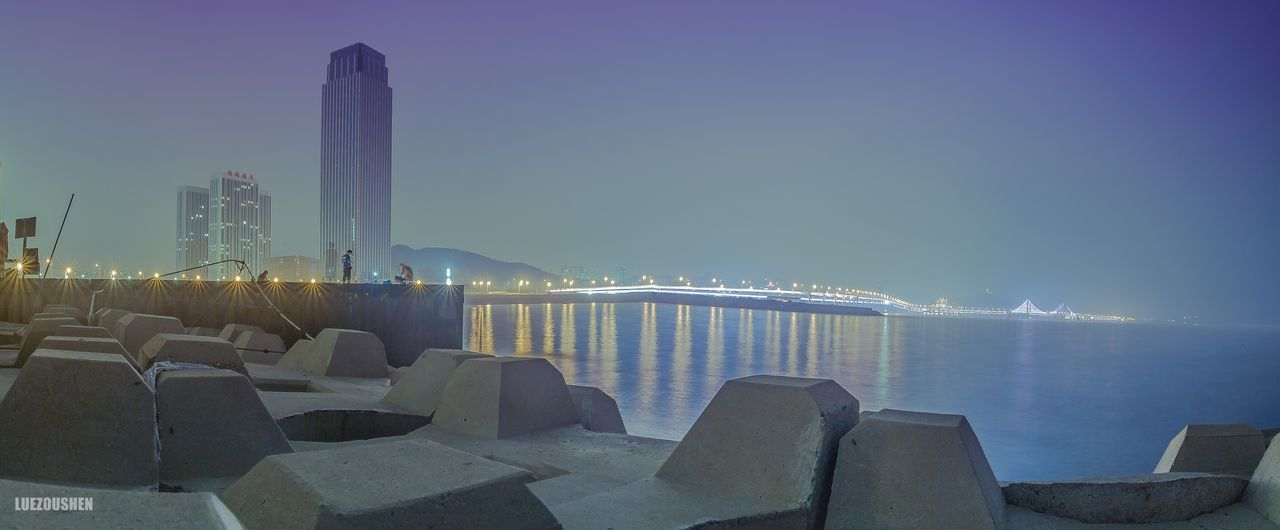illuminated, sea, sky, water, architecture, built structure, no people, night, outdoors, blue, building exterior, nature, skyscraper, beauty in nature, urban skyline, clear sky, city, cityscape