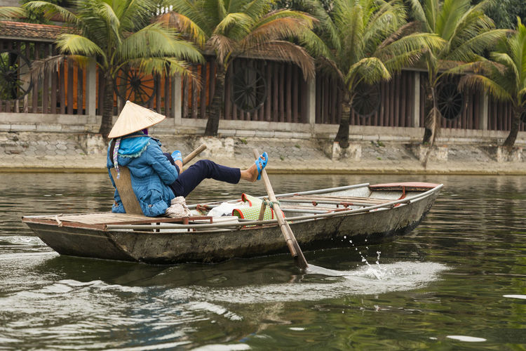 Vietnamese woman in conical hat, bright blue jacket and sandals rowing her boat with her feet at Tam Coc River, with wheels decorating bank wall in the background, Ninh Binh, Vietnam Nautical Vessel Water One Person Mode Of Transportation Outdoors Ninh Binh, Vietnam Tam Coc River Rower Feet Vietnamese Woman Unrecognizable Person Conical Hat Sandals Bank Wall Wheels Decorative Foot Rowing Traditional Tourist Attraction  Transportation Sitting Flat Boat