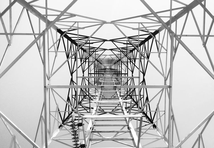 Newly completed telecommunication tower with white and red paint, step ladder in black and white format Bracing Connection Day Design Diminishing Perspective Directly Below Electricity  Electricity Pylon Fuel And Power Generation Galvanized Geometric Shape Ladder Outdoors Power Line  Power Supply Sky Steel Tower  Tall Tall - High Technology Telecommunication