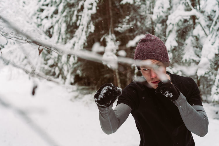 Man jumping by snowy tree