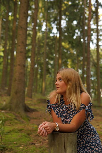 Thoughtful young woman looking away while standing by tree stump in forest