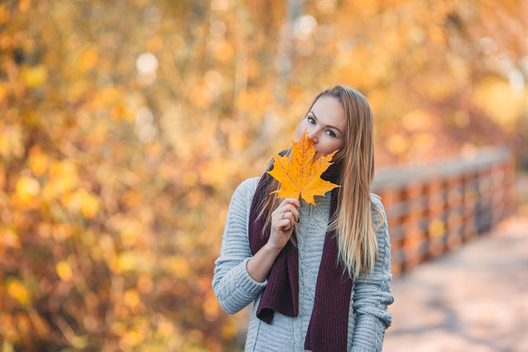 Close-up of woman holding autumn leaf against tree