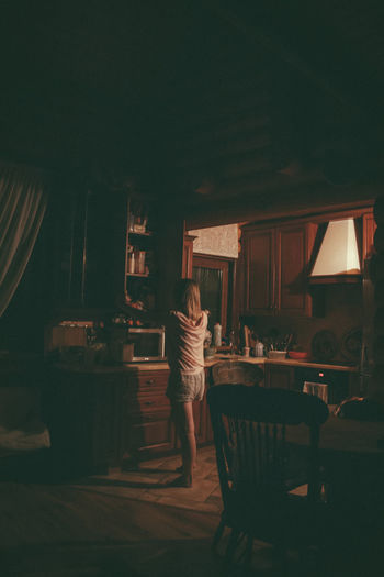 Woman searching in kitchen at home