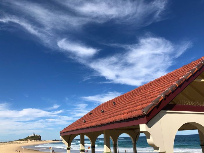 Doves on a hot tile roof, Nobbys Beach pavilion and lighthouse. Colours Strong Contrast Dynamic Striking Cloud Formations Lighthouse Headland Nobbys Beach EyeEm Selects Architecture Built Structure Roof Sky Building Exterior Cloud - Sky Outdoors Day Blue No People Low Angle View Nature