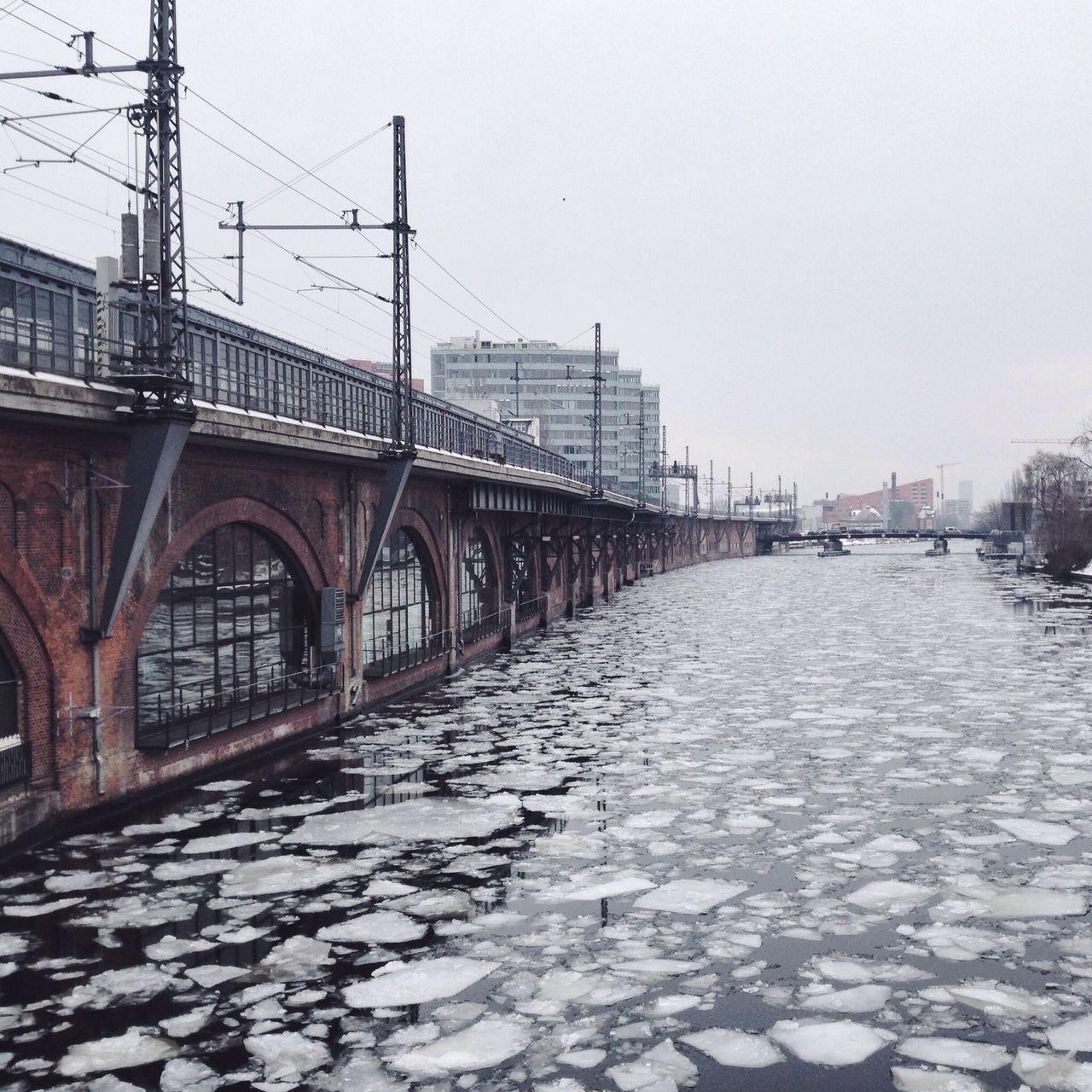 Frozen river by bridge against clear sky