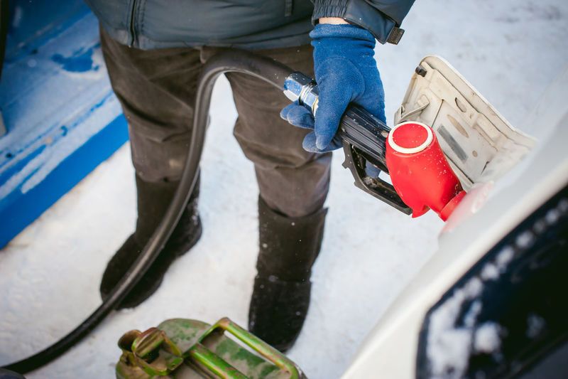 Low section of man refueling car with fuel pump during winter