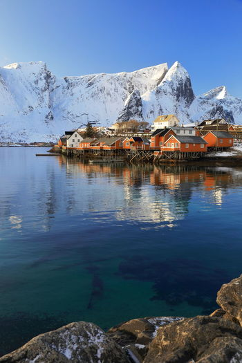 Stilt houses by lake against snowcapped mountains