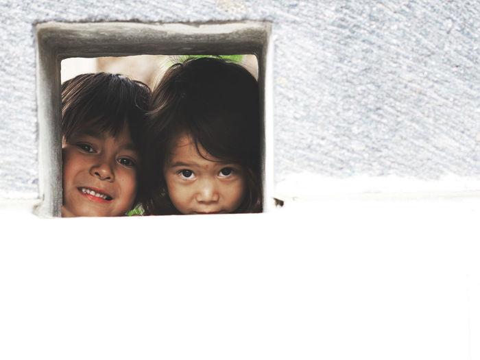 Portrait of siblings looking through window