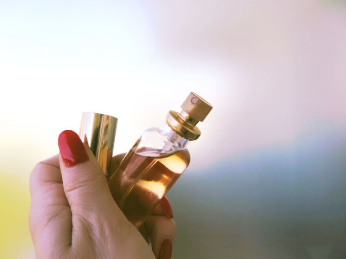 Cropped hand of woman holding perfume