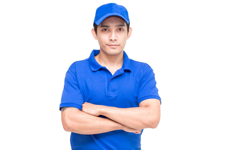 Portrait of salesman with arms crosses standing against white background
