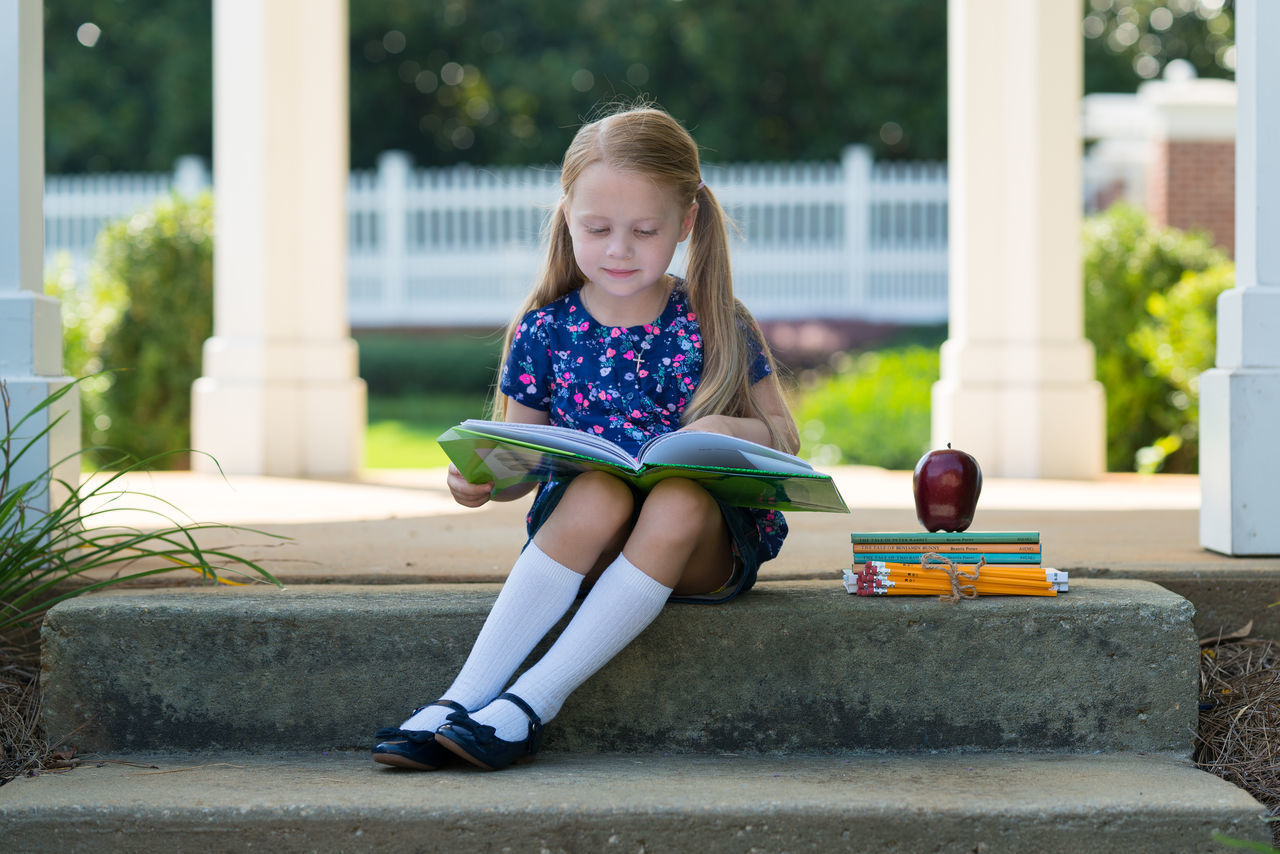Full length of a girl reading book