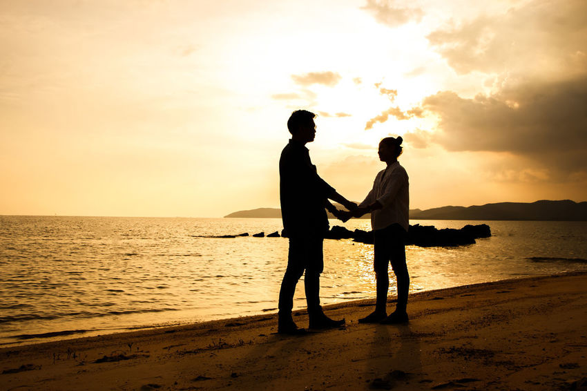 silhouette of people at the beach,The beauty of natural light at sunset. Sunset Sky Two People Water Sea Land Beach Togetherness Silhouette Real People Beauty In Nature Men Standing Leisure Activity Love Scenics - Nature Lifestyles Cloud - Sky Bonding Positive Emotion Couple - Relationship Horizon Over Water Outdoors Son Silhouette Happiness Happy People Holiday Relaxing Children Women Man Romantic Orange Clouds And Sky Love Family Summer Sunrise Boy Freshair Freedom Fun